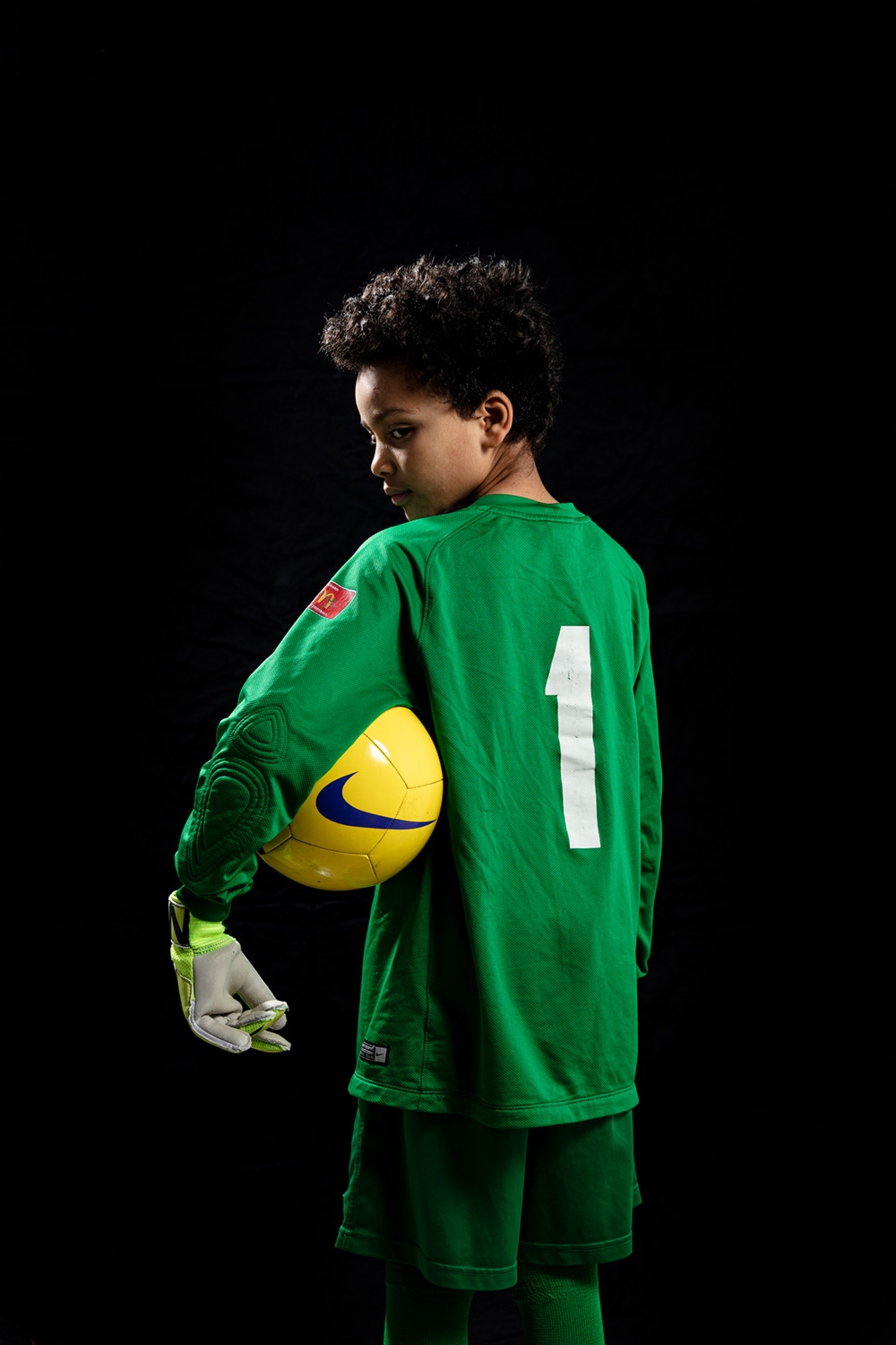 Child wearing a green goalkeeper's uniform with the number '1', looking over their shoulder, holding a yellow football under their arm