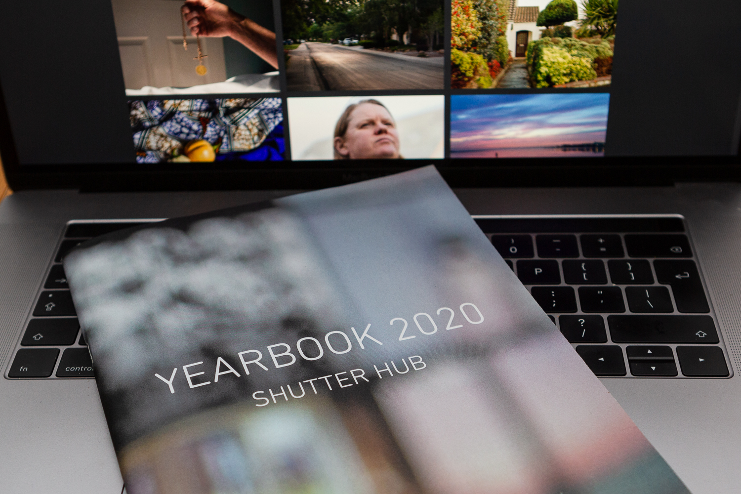 The YEARBOOK 2020 publication lying on the keyboard of a laptop, with images from the online exhibition on the screen behind.