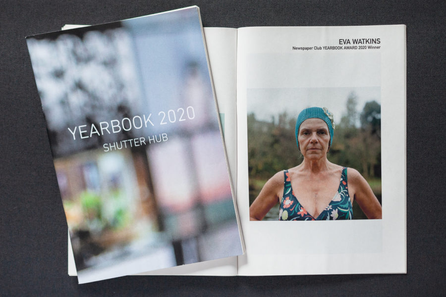 YEARBOOK 2020, one copy to the left showing the front cover with out of focus image and 'YEARBOOK 2020, Shutter Hub' in text, and an open copy underneath, opened to show 'EVA WATKINS, Newspaper Club YEARBOOK 2020 Award Winner' and an image of a synchronised swimmer
