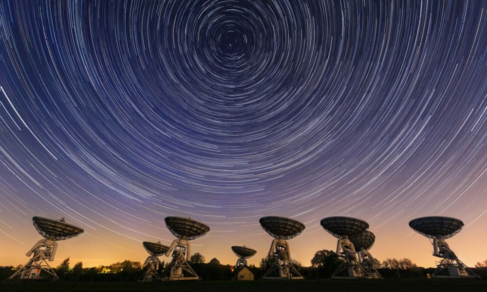 Long exposure photograph of satellites angled up and light trails of stars making circle patterns in the night sky above