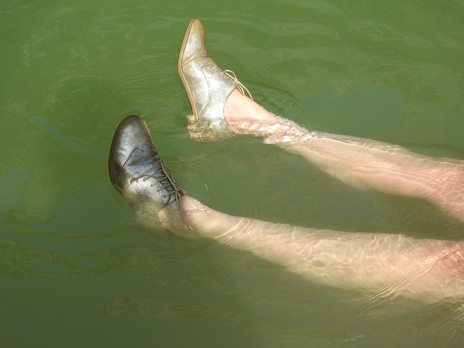Photograph of legs with worn gold shoes floating in greenish water