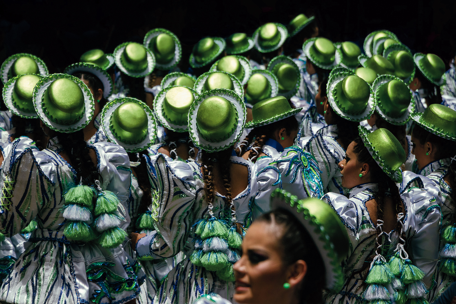 Photograph of Caporales at Carnaval de Oruro, wearing shiny green hats.