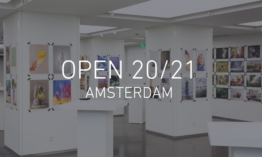 Image of the OPEN 2018 Amsterdam exhibition, with Newspaper Club prints taped to walls and pillars at 5&33 Gallery, with text reading 'OPEN 20/21 AMSTERDAM' in the centre