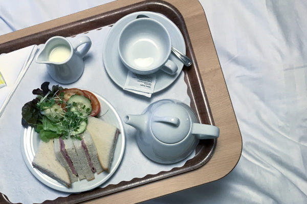 Photograph looking down at a tray containing an empty cup and saucer, a small teapot, a jug of milk and a plate with triangular ham sandwiches and salad to the left