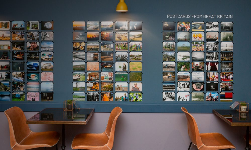 Photograph of chairs and tables in front of the 'Postcards from Great Britain' exhibition in Haarlem, The Netherlands, with postcard-sized photographs taped to a blue wall