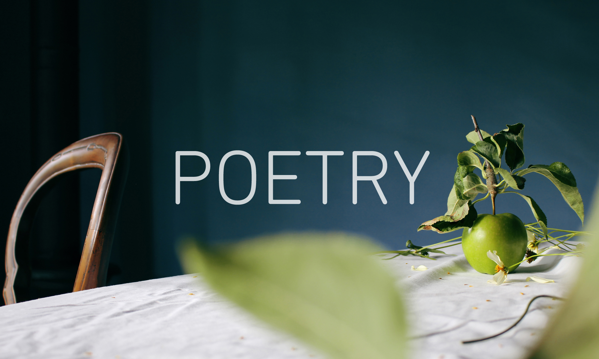 Image of a green apple on a white table cloth to the right, a wooden chair back to the left, and the word 'POETRY' in the centre