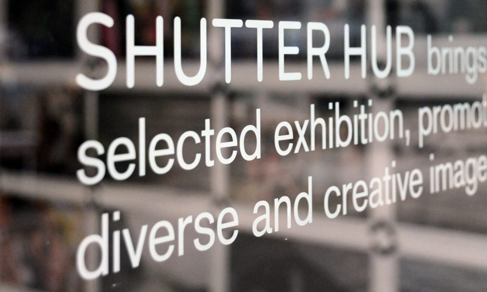 Photograph of white text on a window, with photographs from an exhibition out of focus in the background. The text says 'SHUTTER HUB brings, selected exhibition, promoting, diverse and creative images'
