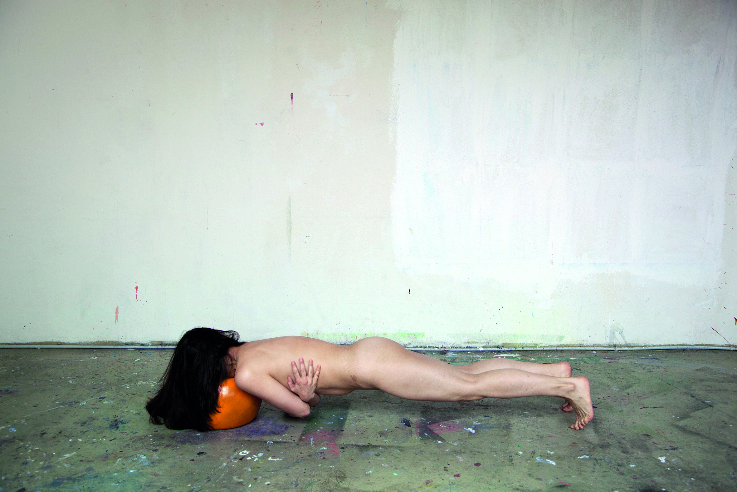 A naked woman in a plank position on the floor of what appears to be an artist's studio, head resting on an orange ball