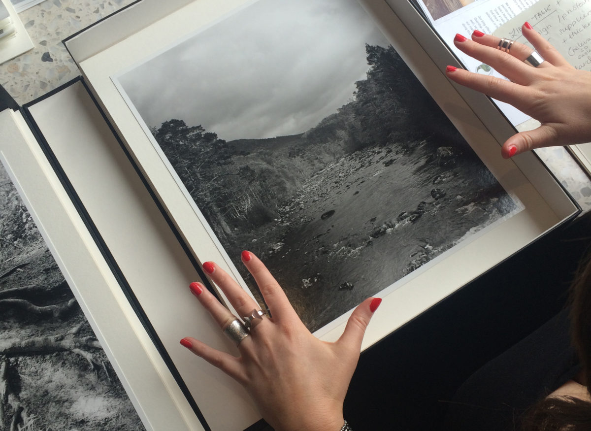 Hands with red painted nails and ornate rings either side of a box with a black and white photograph